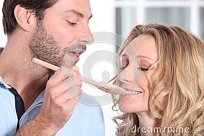 Wife sampling husband s cooking