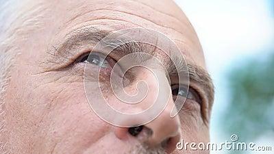 Wijsheid in ogen van de oude mens die op close-up, hogere persoon kijken die over verleden denken stock videobeelden