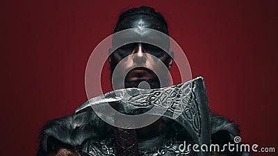 Wiking w wojennej farbie pochyla brodę na siekierze, otwiera oczy i patrzy agresywnie na kamerę Menacing Viking zdjęcie wideo