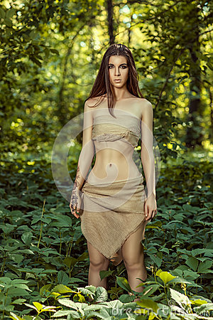 Savage woman with long hair standing in the woods