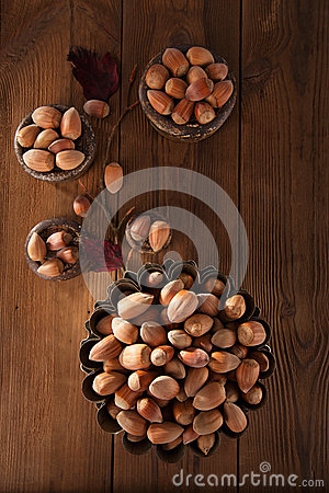 Wild hazelnut in iron bowls on wooden table