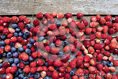 Wild strawberry and bilberry on a  table