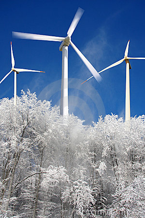 Wind mills power generators against winter forest