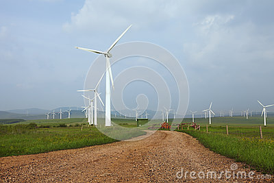 Wind turbine on the green grass over the clouded