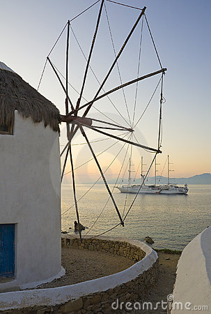 Windmill against sunset and cruise ship