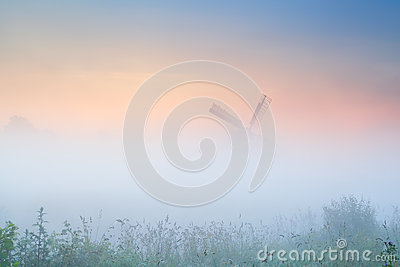 Windmill in dense fog at sunrise