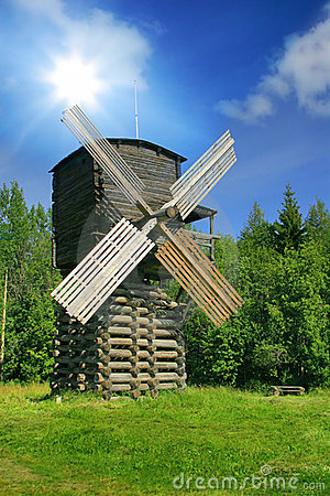 Windmill in forest under sun