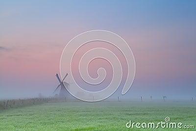 Windmill silhouette over sunrise sky