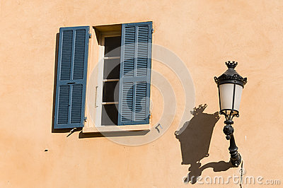 Window with blue shutters and old streetlamp