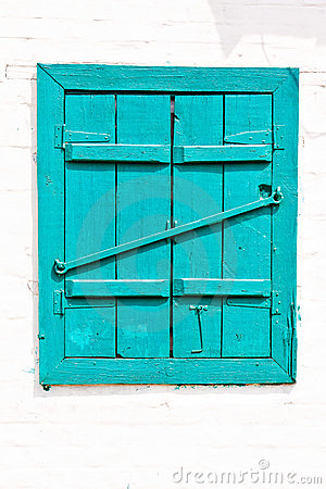 Window with closed wooden painted blue shutters