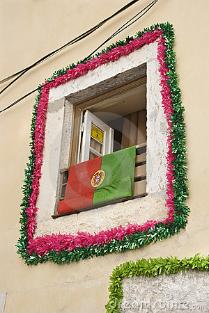 Window with garland and flag in Portugal.