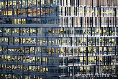 Windows of a business tower showing people at work