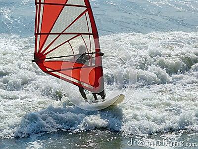 Windsurfer red sail white surf