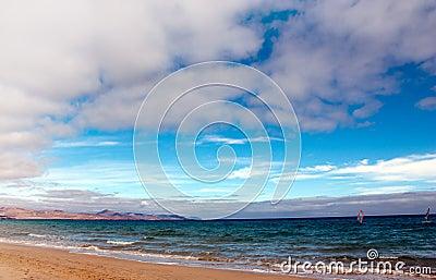 Windsurfing along long empty beach