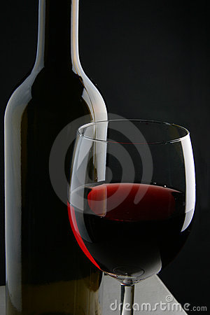 Wine bottle and glass over black background