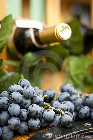 Wine bottle, grape an leaves on a wood barrel