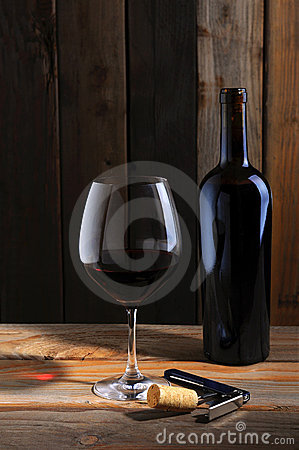 Wine bottle and wineglass in cellar setting