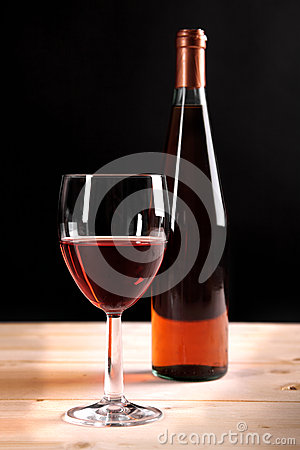 Wine collection: Rose wine glass and bottle on wooden table