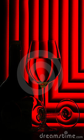 Wine glasses and bottle on red