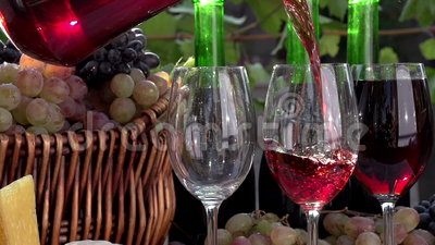 Wine Tasting. In pouring a glass of wine on the background of a basket with grapes, wine bottles and pieces of cheese. Slow Motion at a rate of 240 fps stock video