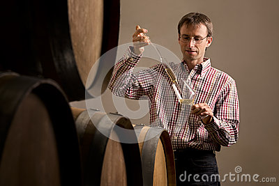 Winemaker in cellar making wine test.