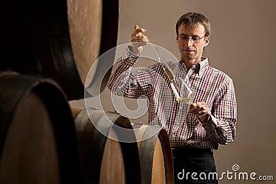 Winemaker in kelder die wijntest maakt.