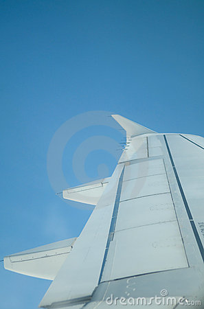 Wing of airplane against a blue sky