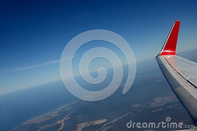 Wing of plane above Earth. Blue sky.