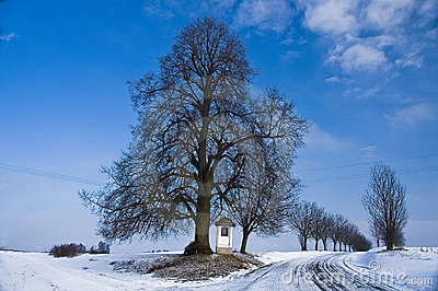 Winter country road with a village chappel