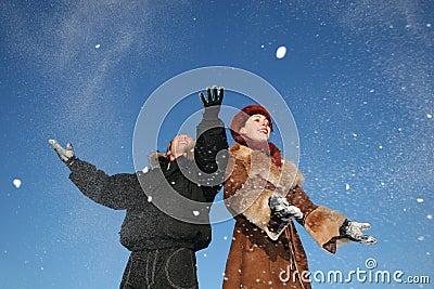 Winter couple throw snow
