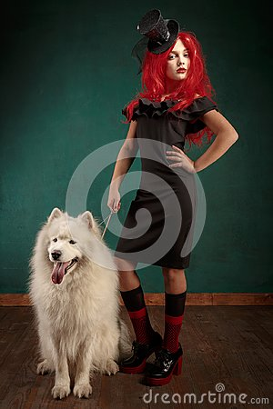 Free Winter Dog Holiday And Christmas. Girl In A Black Dress And With Red Hair With A Pet In The Studio. Christmas Woman With Royalty Free Stock Photos - 105603938