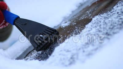 Winter driving - scraping ice from a windshield stock footage