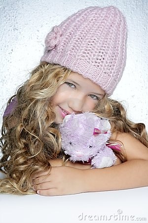 Winter fashion little girl hug teddy bear smiling