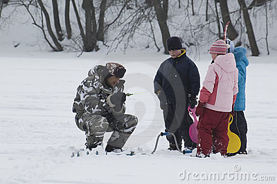 Winter fishing. Old Fisherman and young spectators Editorial Photo