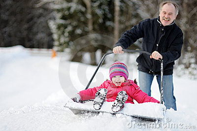 Winter fun: having a ride on a snow shovel