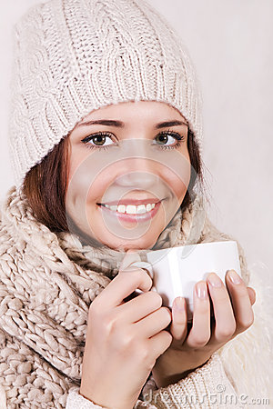 Winter girl drinking warm beverage.