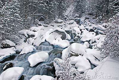 Winter mountain creek cascades and snowfall