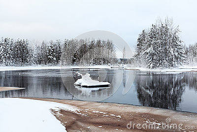 Winter shore of unfrozen lake with melted water