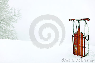 A winter snow scene background with a red vintage upright sled.