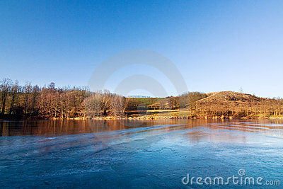 Winter/spring landscape with frozen pond