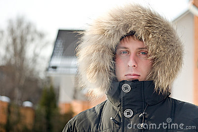 Winter time - man in warm jacket with furry hood