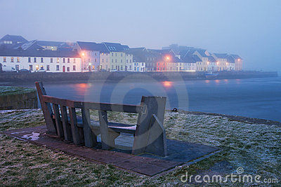 Winter view on the river and houses in fog