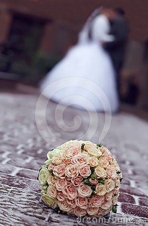 Winter wedding bouquet on snow on kiss background