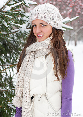 Winter woman behind snow tree