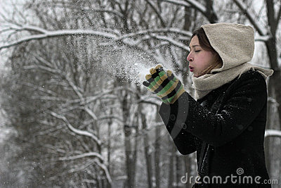 Winter woman blowing a snow