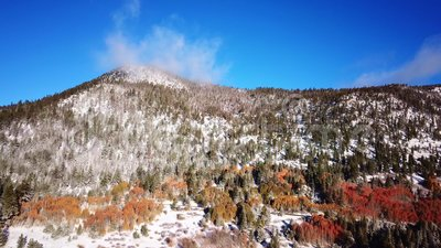 Wintery fall mountain slide with snow and autumn colors stock video