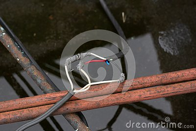 wires are interconnected and insulated with electrical tape on the street on the roof of the plant. Stock Photo