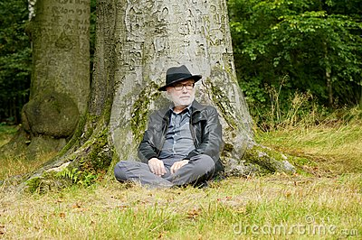 Wise old man sitting under tree in the forest
