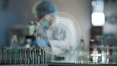 Wissenschaftler, der Mikroskop vor der Untersuchung von Blutproben des Patienten im Labor justiert stock footage
