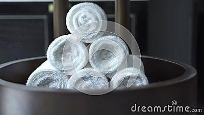 Wit handdoekbroodje in moderne kuuroordsalon op donkere achtergrond Witte badhanddoek in donkere badkamers Toebehoren voor douche stock videobeelden